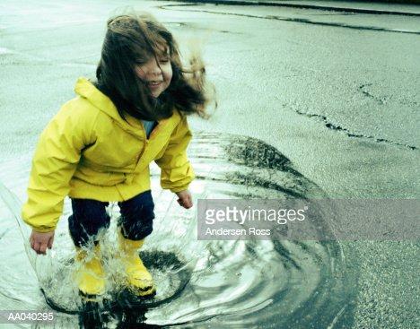 Girl (3-5) jumping in puddle wearing rain gear : Stock Photo
