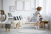 Blonde girl in dress jumping in modern room with swing