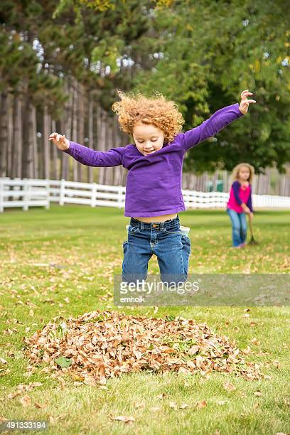 Girl Jumping in Small Pile of Autumn Leaves