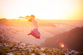 Girl jumping in snow with sunset in winter
