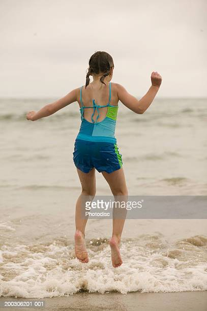 Girl (12-13) jumping in surf, rear view