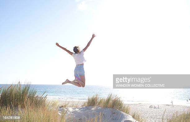 Girl jumping in the air off sand dunes at beach