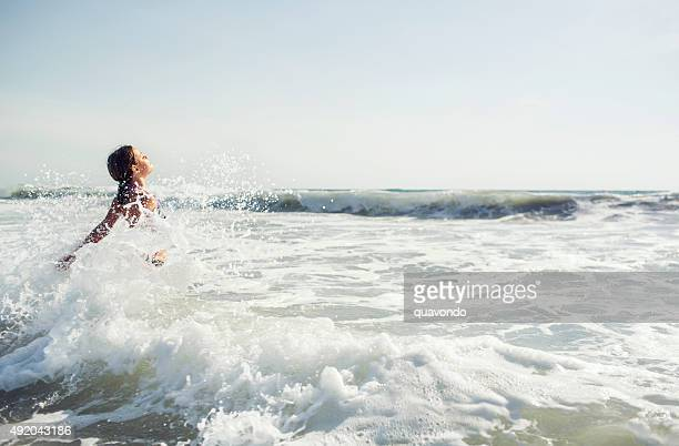 Girl jumping in the waves