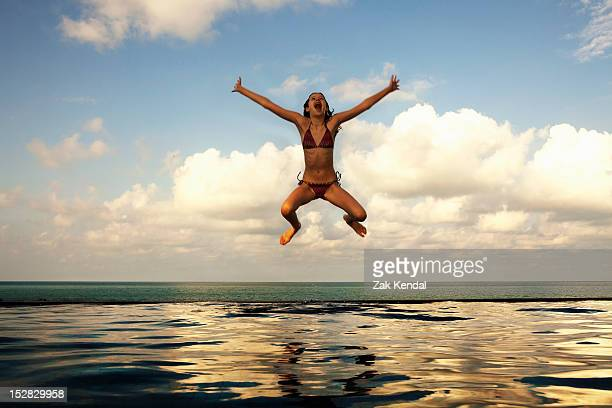 Girl jumping into infinity pool