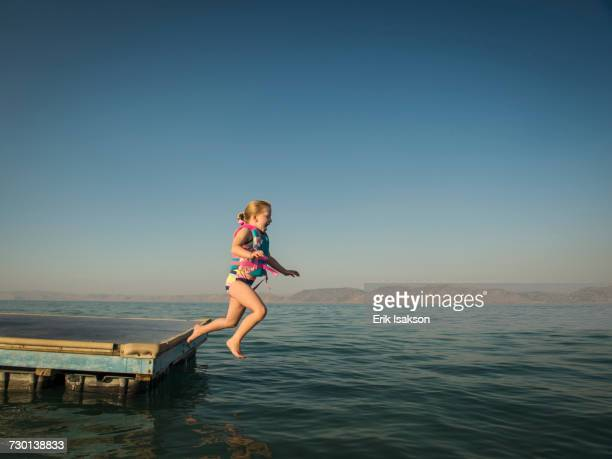 Girl (4-5) jumping into lake from pier