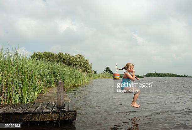 Girl jumping into rural lake