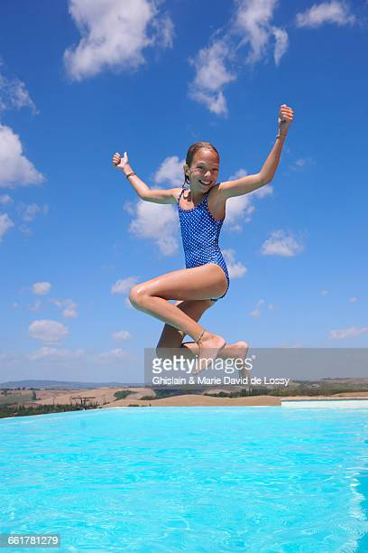 Girl jumping into swimming pool, Buonconvento, Tuscany, Italy