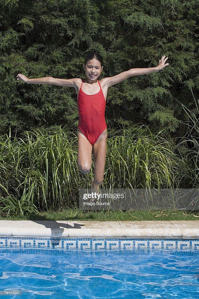 girl jumping into swimming pool stock photo getty images
