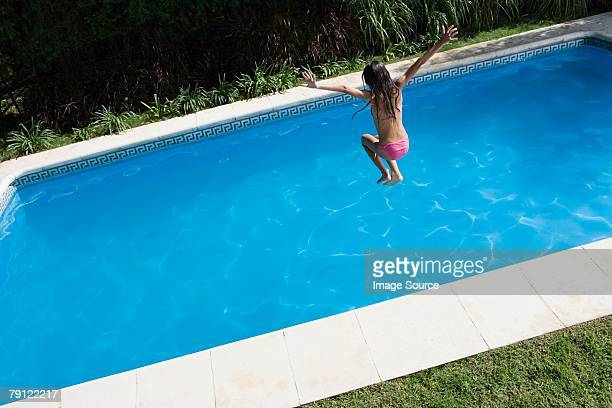 Girl jumping into swimming pool