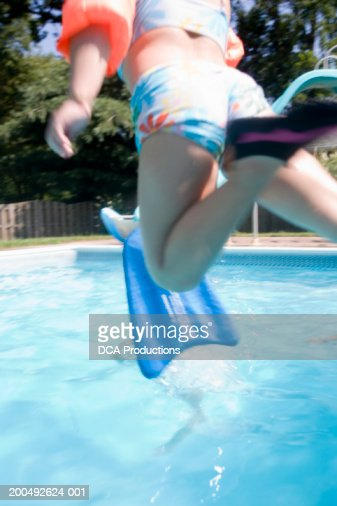 Girl Jumping Into Swimming Pool Rear View Mid Section Stock Photo Getty Images