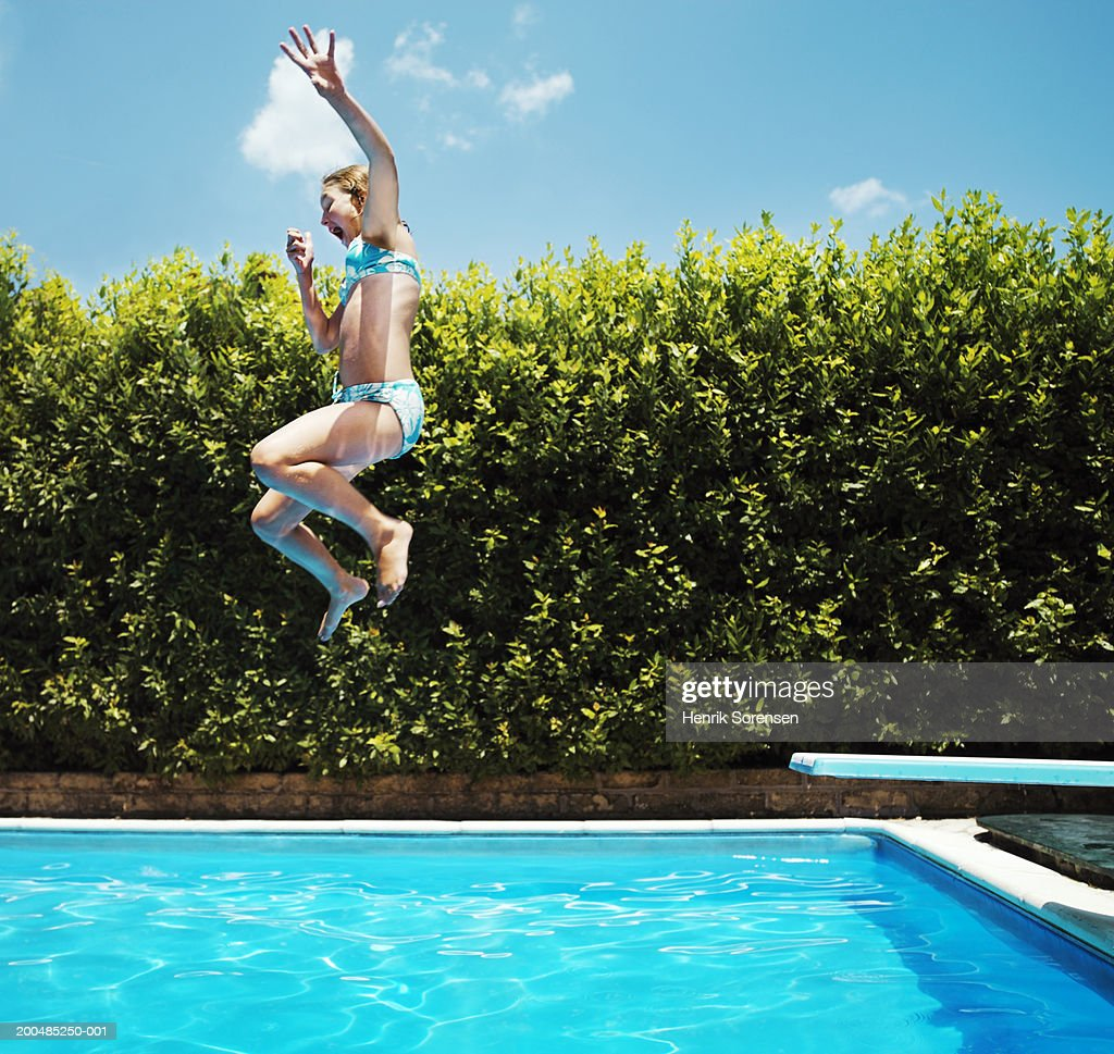 Girl Jumping Into Swimming Pool Side View Stock Photo Getty Images