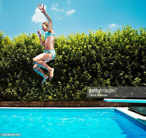 Girl (10-12) jumping into swimming pool, side view