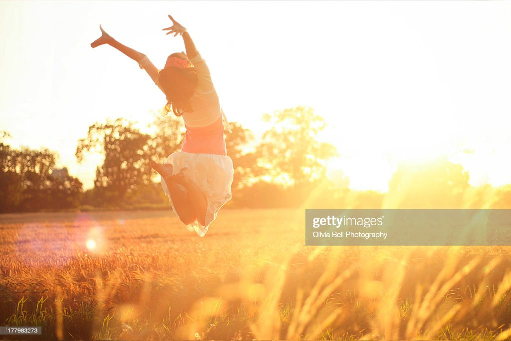 Girl jumping into the sunshine : Stock Photo
