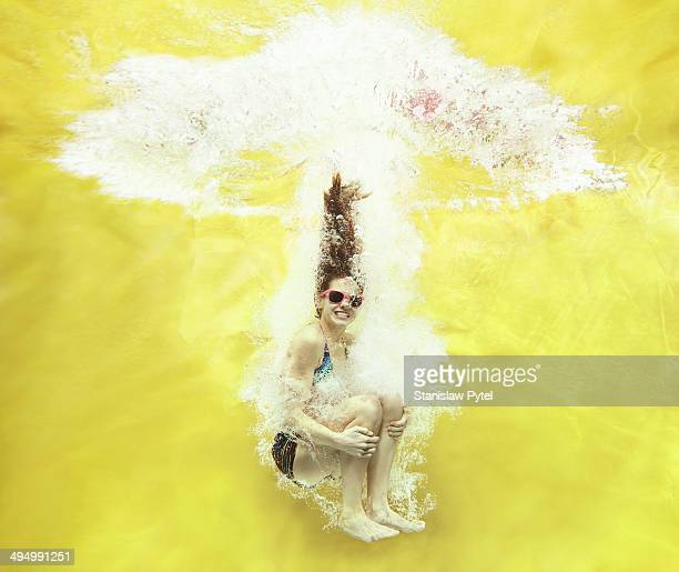 Girl jumping into water on yellow background