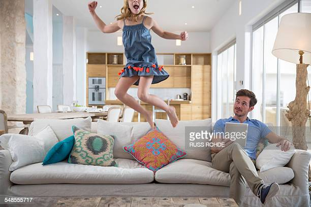 Girl jumping mid air from living room sofa whilst father uses digital tablet