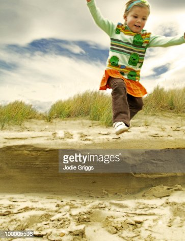 Girl jumping off a Sand Dune : Stock Photo