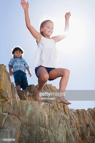 Girl jumping off boulder outdoors