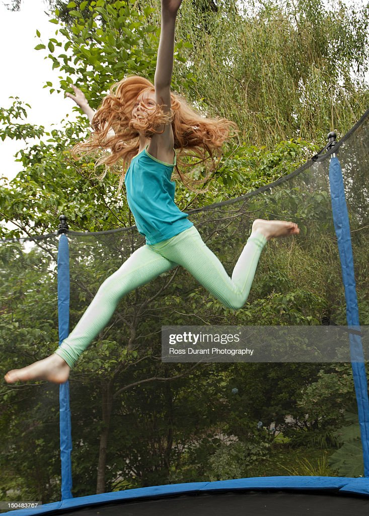 A girl jumping on a trampoline in a garden : Stock Photo