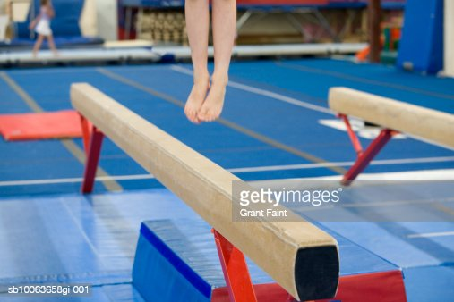 Girl (16-17) jumping on balance beam in gym, low section