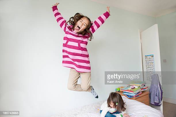 Girl jumping on bed and pulling face