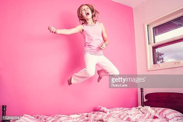 Mädchen springen auf dem Bett in Rosa Zimmer