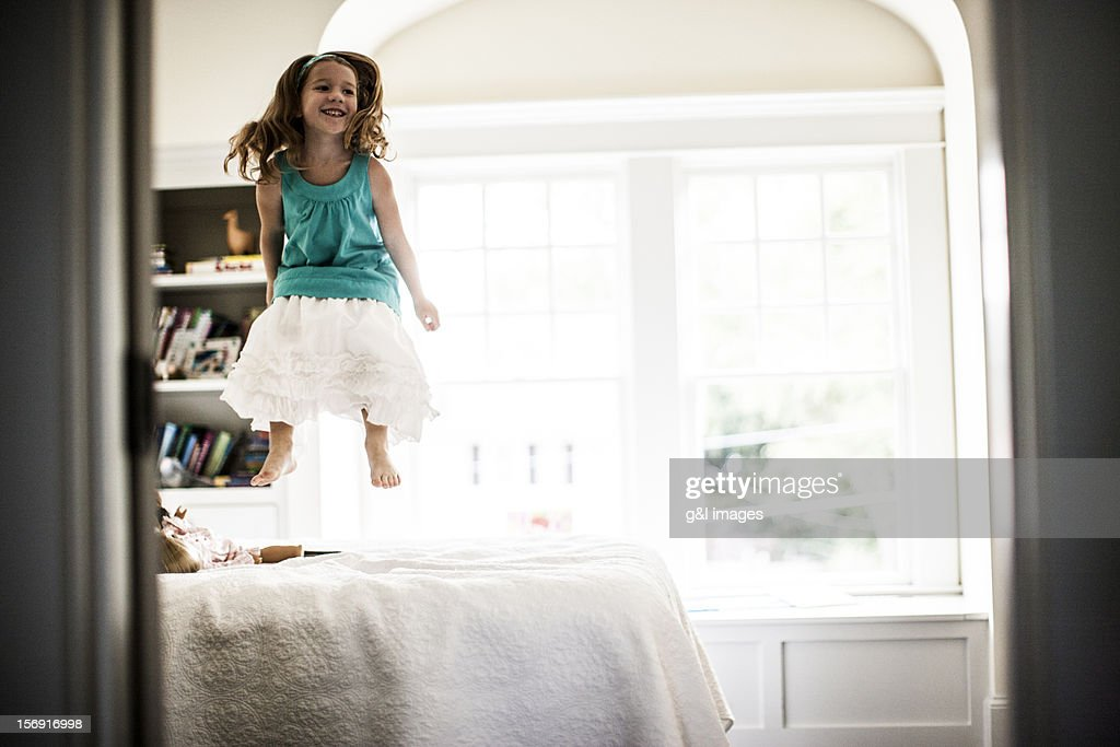 Girl (6yrs) jumping on bed : Stock Photo