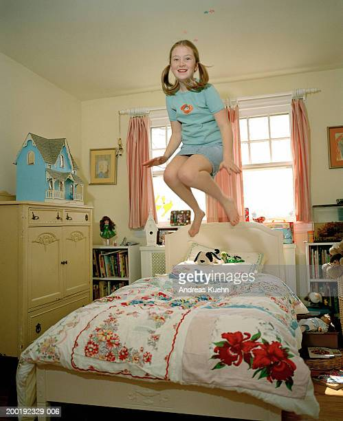 Girl (8-10) jumping on bed, smiling, portrait