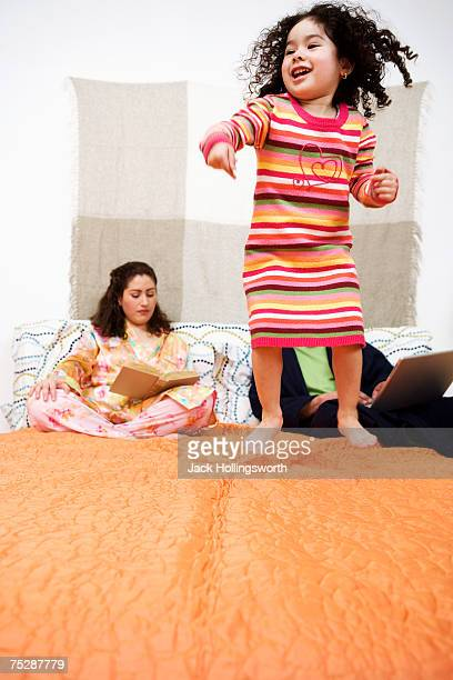 Girl (2-3) jumping on bed with parents sitting behind
