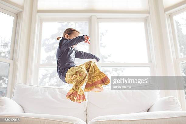 Girl jumping on couch