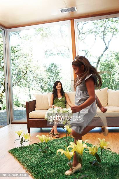 Girl (6-7 Years) jumping on grass patch with flower in living room, mother watching