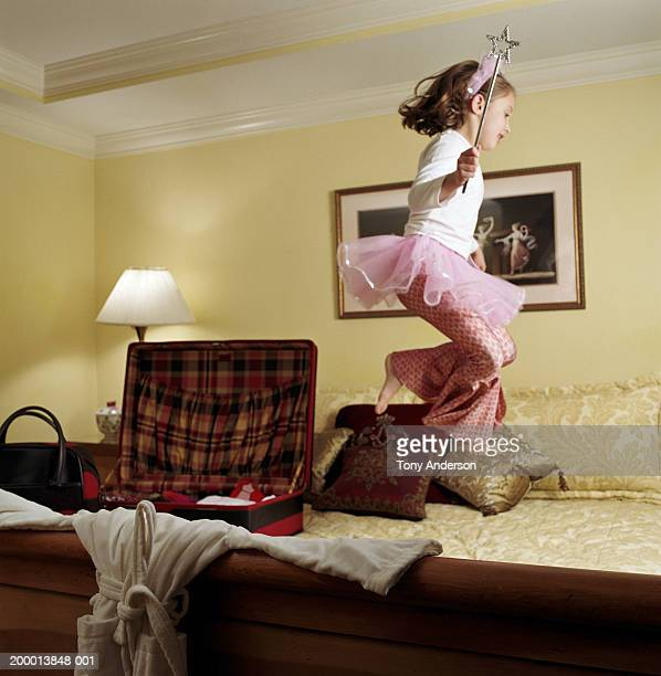 Girl (4-6) jumping on hotel room bed, wearing angel costume, profile