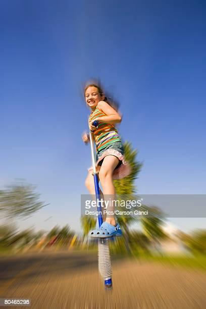 Girl jumping on pogo stick