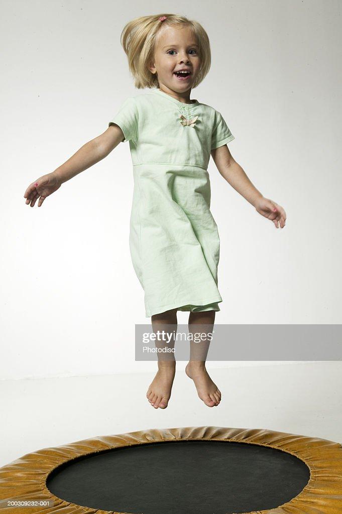 Girl (6-7), jumping on trampoline in studio, portrait : Stock Photo