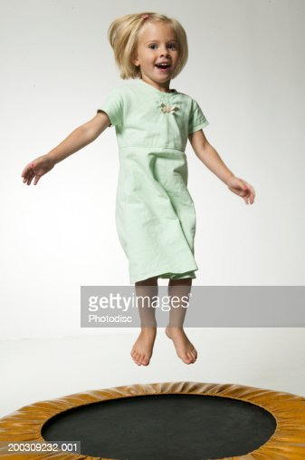 Girl (6-7), jumping on trampoline in studio, portrait : Stock Photo