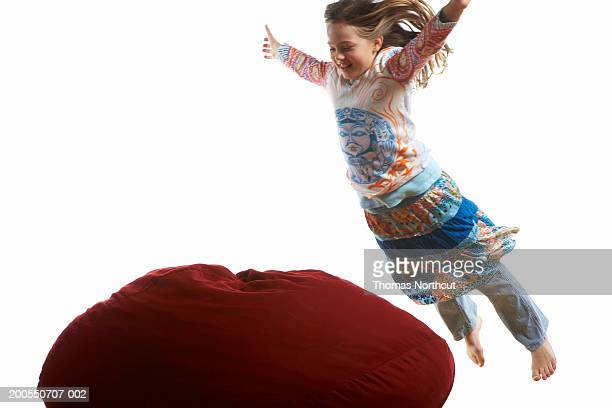 Girl (7-9) jumping onto bean bag, arms outstretched