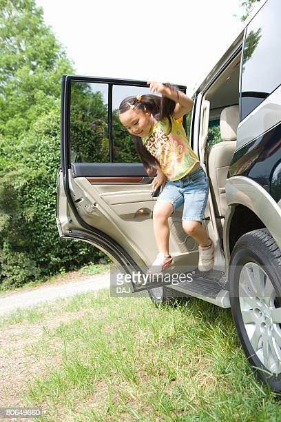 Girl jumping out of a car, summer