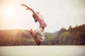 Girl Jumping over Lake