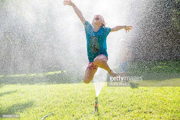 Girl jumping over water sprinkler in garden