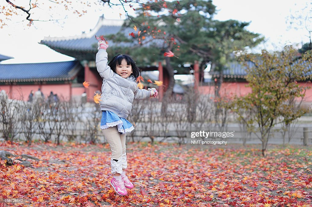 Girl jumping playing with falling leaves : Stock Photo