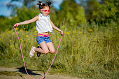 little girl jumping rope on nature