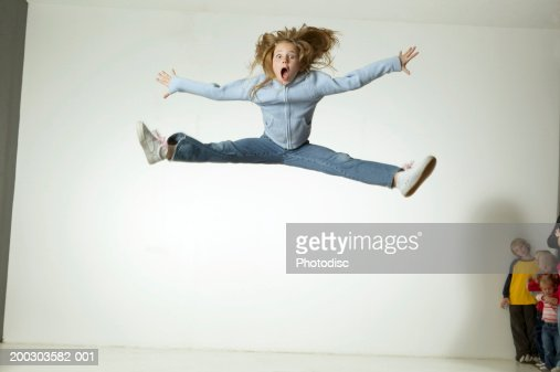 Girl (6-7), jumping with arms and legs outstretched, on trampoline in studio, portrait