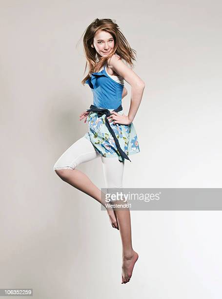 Girl (12-13) jumping with hand on hip, smiling, portrait