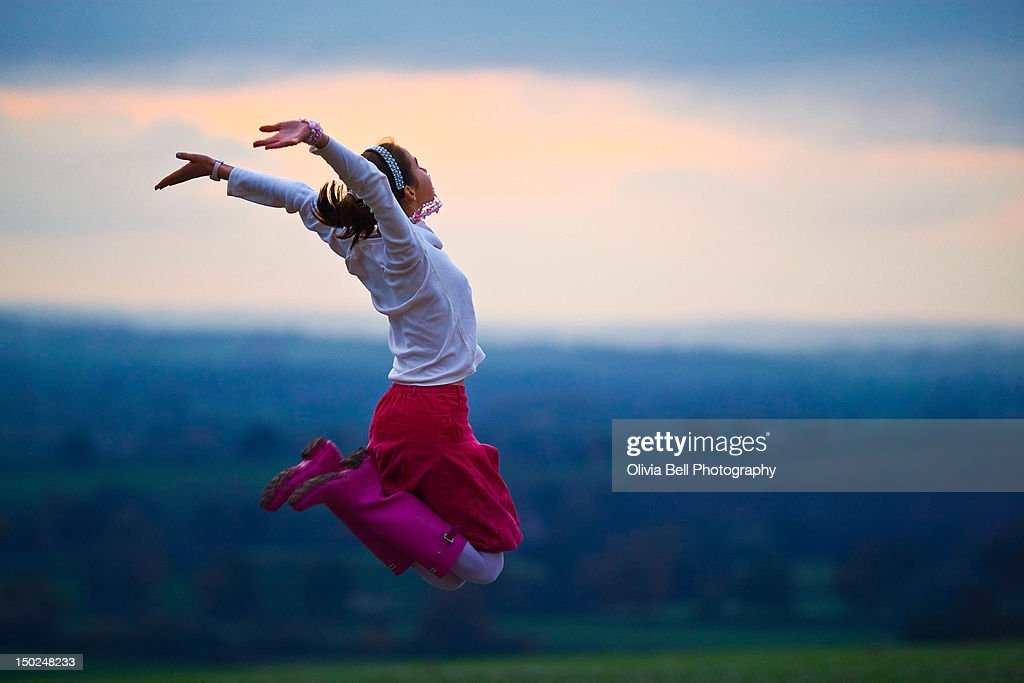 Girl jumping with hands in air wearing pink boots