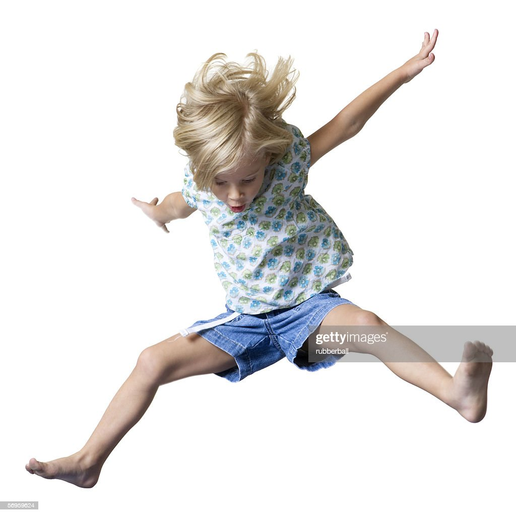 Girl jumping with her legs and arms stretched out : Stock Photo