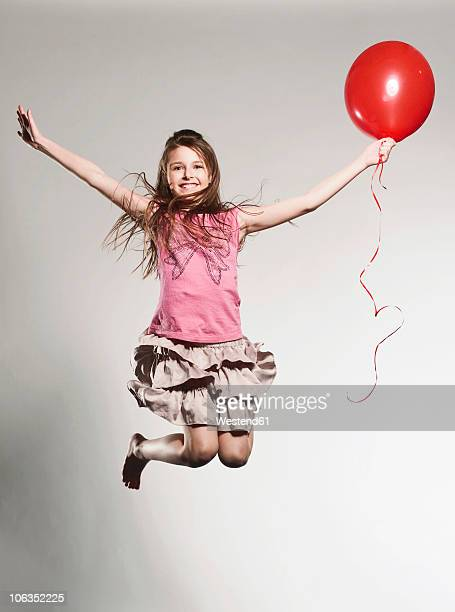 Girl (8-9)  jumping with holding balloon, smiling, portrait