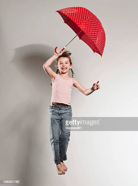 Girl (6-7) jumping with holding umbrella, smiling, portrait