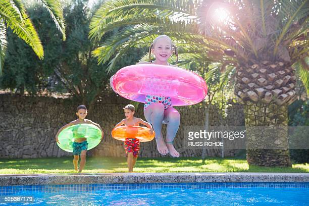 Girl jumping with inflatable ring into garden swimming pool