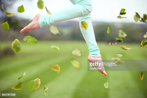 Girl Jumping with Leaves Falling