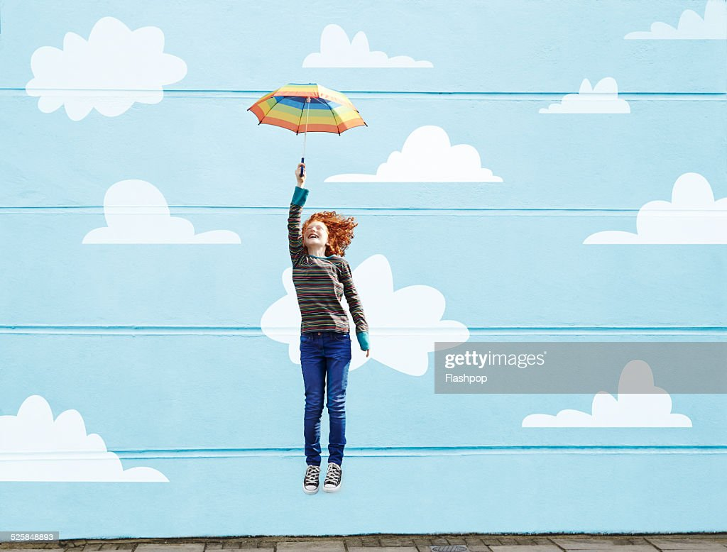 Girl jumping with umbrella : Stock Photo