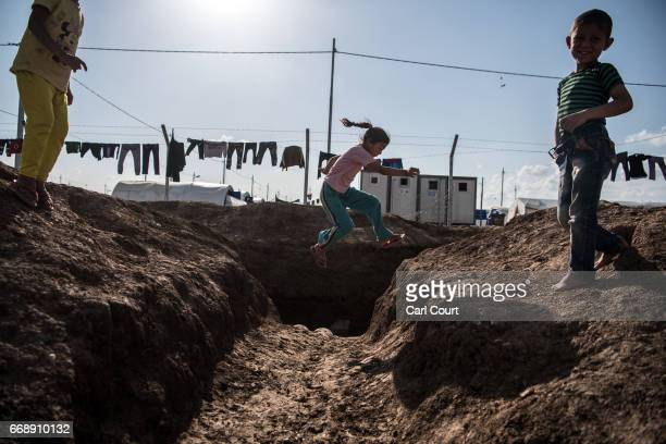 A girl jumps across a ditch next to an open drain in Khazir refugee camp on April 15 2017 near Mosul Iraq Khazir camp with a capacity of roughly...